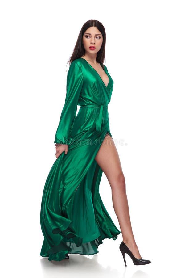 Opinião lateral a mulher no vestido que anda e que olha atrás fotos de stock royalty free