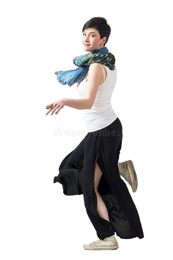 A opinião lateral a mulher nova do cabelo curto no largo-pé arfa o corredor que gira principal para a câmera fotos de stock royalty free