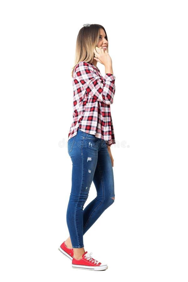 Opinião lateral a mulher nova do estilo da rua que anda e que fala no telefone celular que olha acima imagens de stock