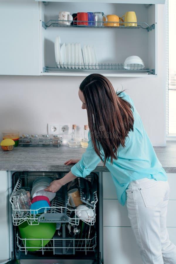 A opinião lateral a mulher puxa pratos limpos da máquina de lavar louça fotos de stock
