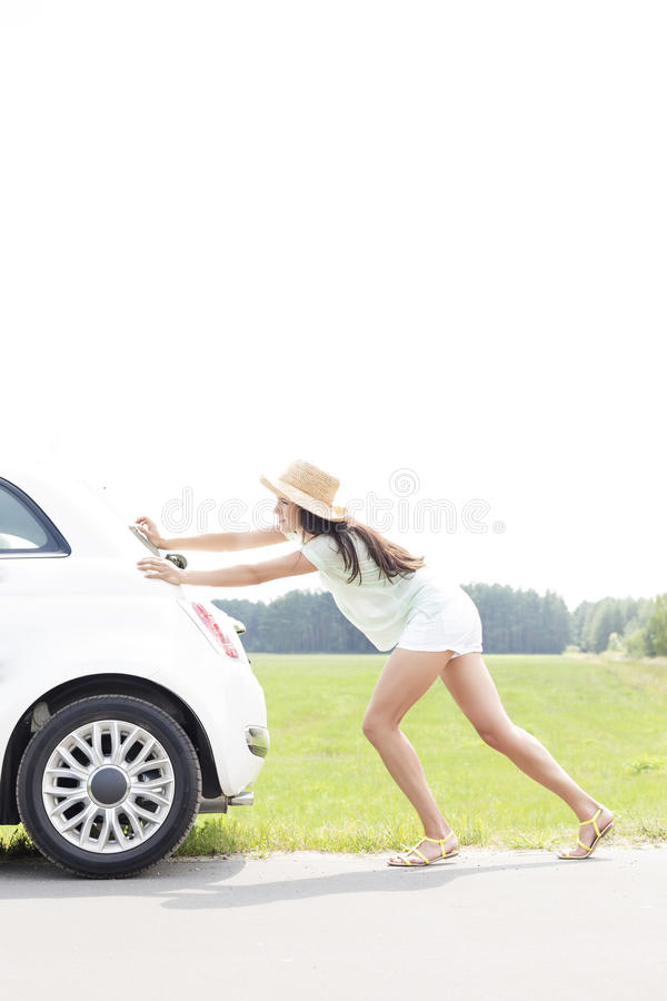 Opinião lateral a mulher que empurra o carro dividido na estrada secundária imagens de stock