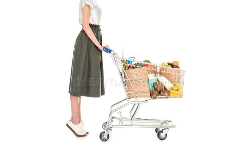 opinião lateral a mulher que está com o trole da compra com sacos de papel e mantimento imagem de stock royalty free