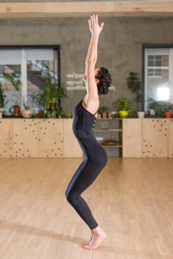 A opinião lateral a mulher que está com suas mãos levantou acima a preparação para o exercício da ioga em um gym imagem de stock