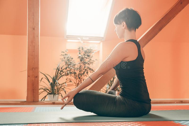 Opinião lateral a mulher que faz o exercício do abrandamento da ioga fotografia de stock royalty free
