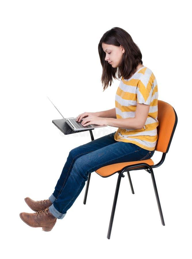 Opinião lateral a mulher que senta-se em uma cadeira para estudar com um portátil fotografia de stock royalty free