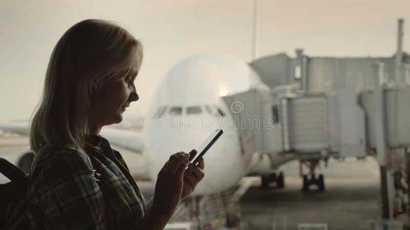 A opinião lateral a mulher usa um smartphone no terminal de aeroporto no fundo de um grande avião de passageiros fora da janela foto de stock royalty free