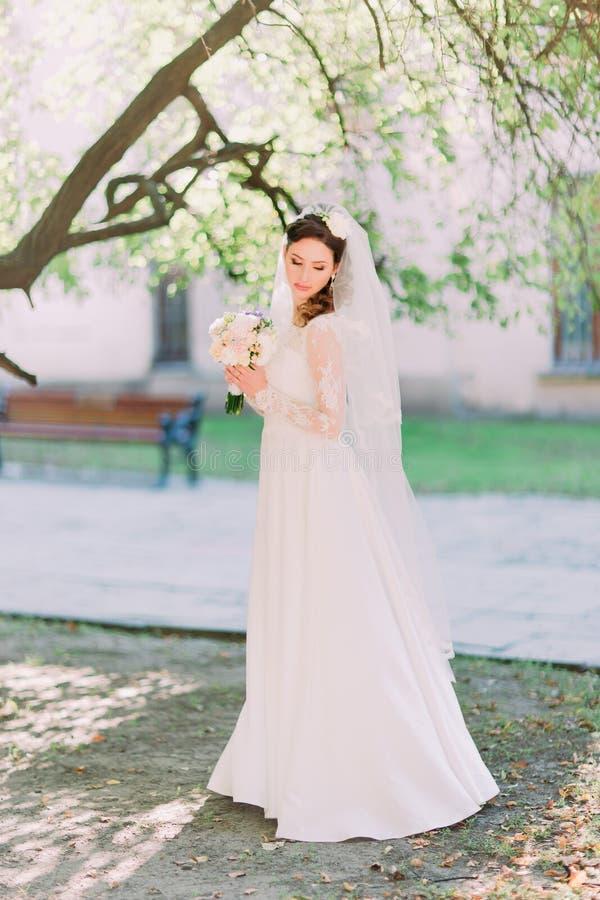 Opinião lateral a noiva tímida que olha abaixo de guardar o ramalhete da flor no jardim, parque foto de stock