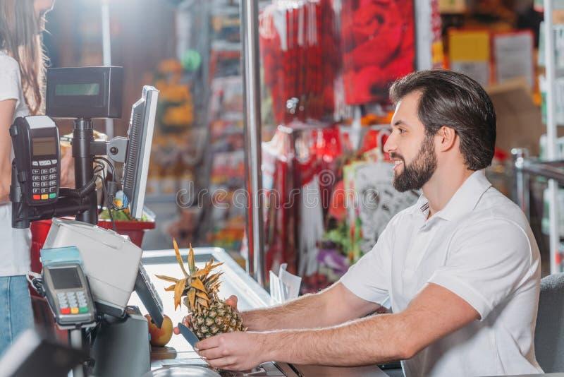 opinião lateral o assistente de loja no ponto do dinheiro fotos de stock royalty free