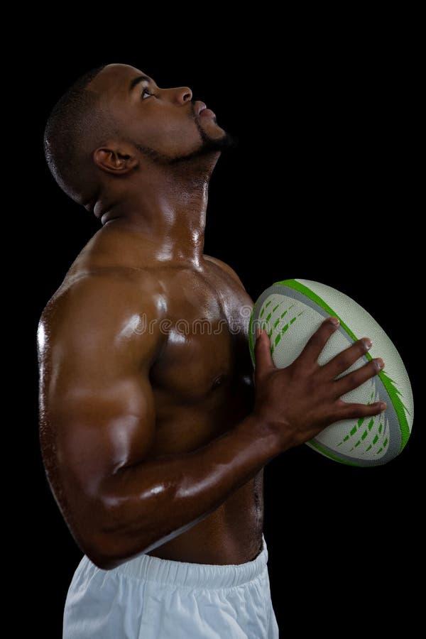 Opinião lateral o atleta masculino descamisado que olha mantendo a bola de rugby fotografia de stock royalty free