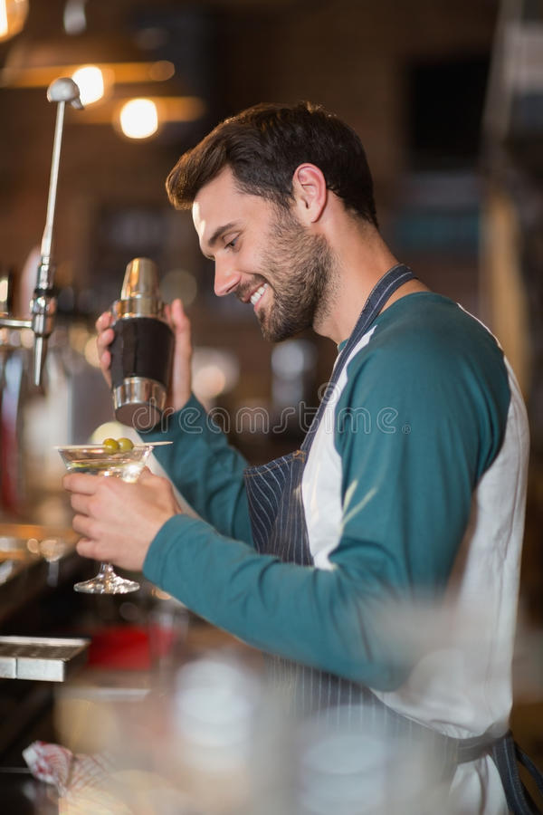 Opinião lateral o barman de sorriso que faz bebidas fotos de stock
