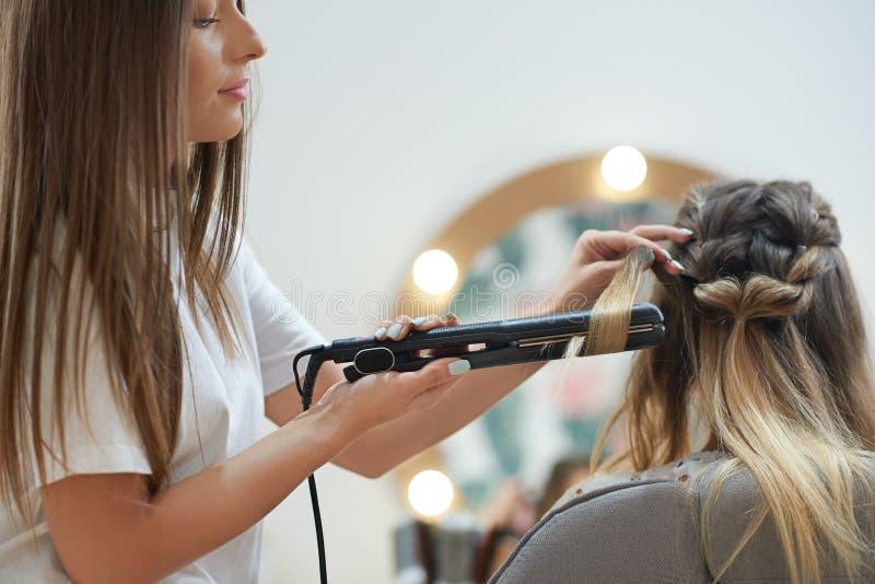 Opinião lateral o cabeleireiro que usa o straightener que faz ondas ao cliente no salão de beleza fotos de stock royalty free