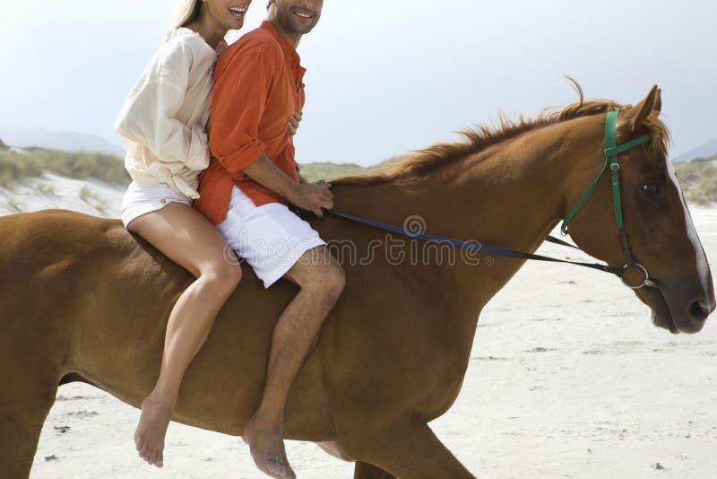 Opinião lateral o cavalo de equitação dos pares na praia fotos de stock royalty free