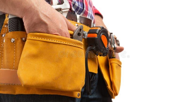 Opinião lateral o construtor que guarda as mãos dentro dos bolsos da correia da ferramenta fotos de stock