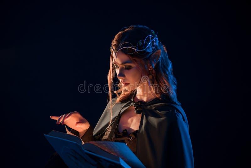 Opinião lateral o duende bonito fêmea místico que lê o livro mágico na escuridão imagens de stock