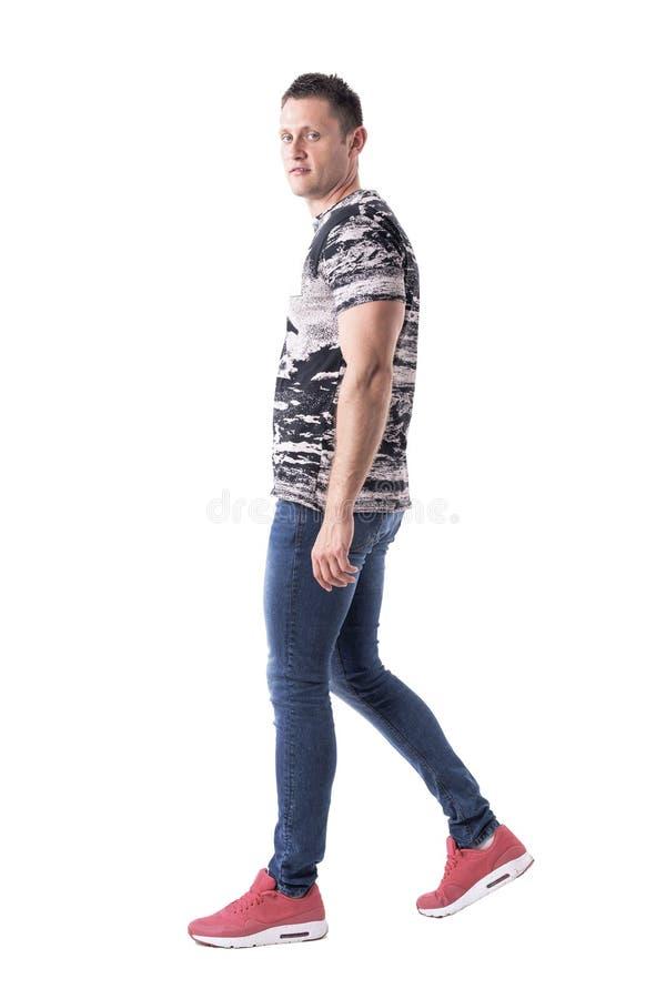 Opinião lateral o homem considerável sério na roupa ocasional que anda e que olha a câmera foto de stock royalty free