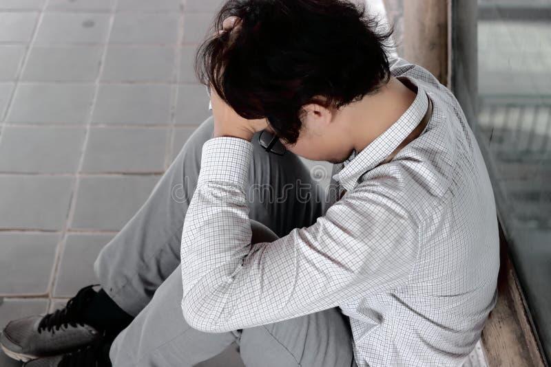 Opinião lateral o homem de negócio asiático novo deprimido ansioso com as mãos que cobrem a cara e que sentem disappionted ou esg imagem de stock royalty free