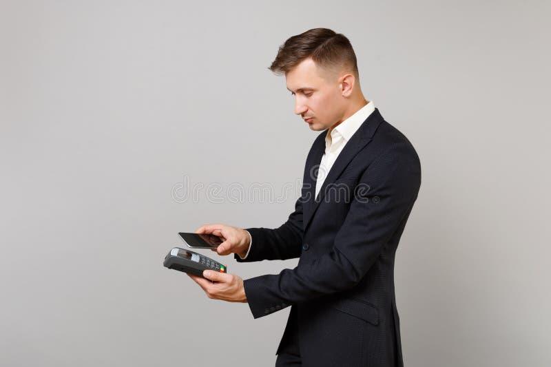 A opinião lateral o homem de negócio guarda o terminal moderno sem fio do pagamento do banco para processar para adquirir os paga foto de stock