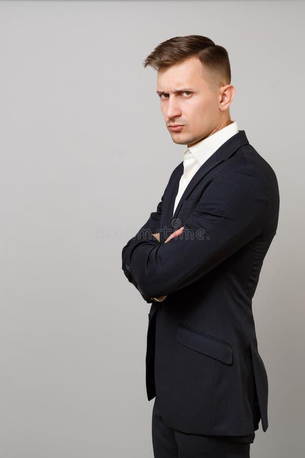 A opinião lateral o homem de negócio novo desagradado no terno preto clássico, mãos da terra arrendada da camisa dobrou-se isolad imagem de stock