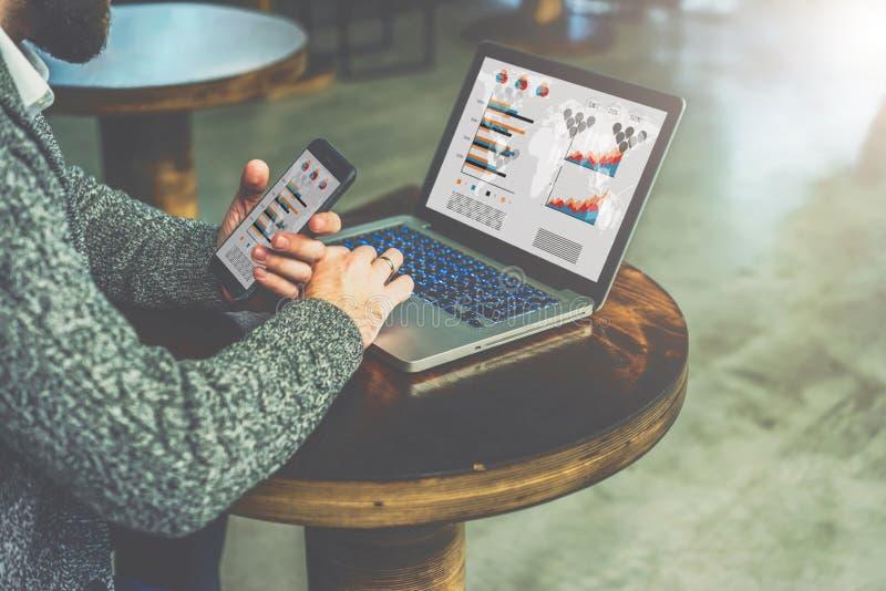 A opinião lateral o homem de negócios farpado novo senta-se de madeira redonda no café e usa-se o portátil com gráficos, cartas fotos de stock
