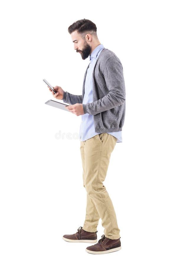 Opinião lateral o homem de negócios farpado ocupado que usa a tabuleta e o passeio esperto do telefone fotografia de stock