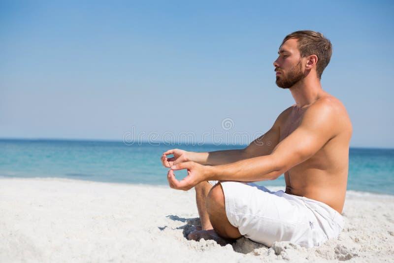 Opinião lateral o homem descamisado que medita na praia foto de stock