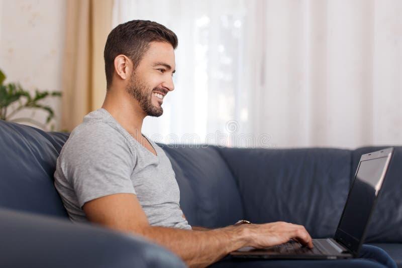 Opinião lateral o homem novo considerável que usa seu portátil fotografia de stock