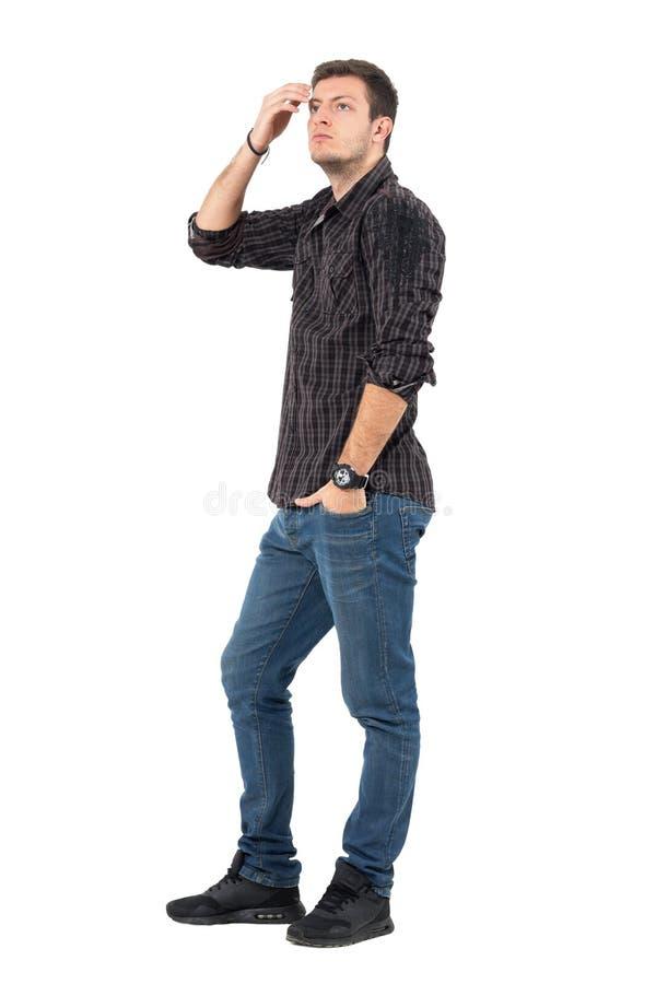 Opinião lateral o homem novo ocasional nas calças de brim e na camisa de manta que ajustam o cabelo com a mão que olha acima imagem de stock royalty free