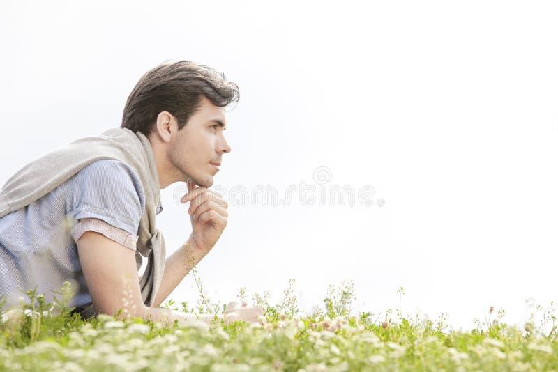 Opinião lateral o homem novo pensativo que encontra-se na grama contra o céu claro fotografia de stock