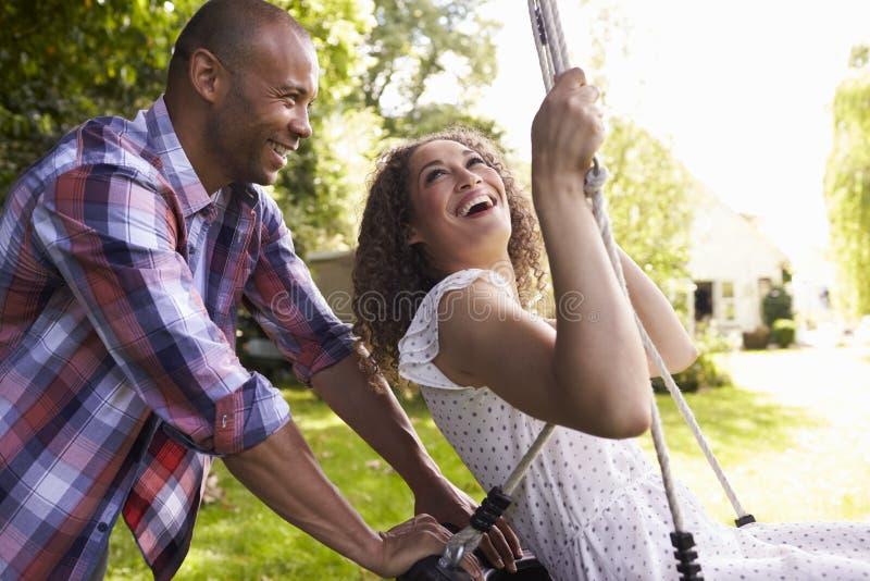 Opinião lateral o homem que empurra a mulher no balanço do pneu no jardim imagens de stock