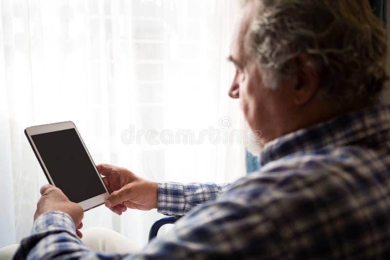 Opinião lateral o homem superior que usa a tabuleta digital no lar de idosos imagens de stock