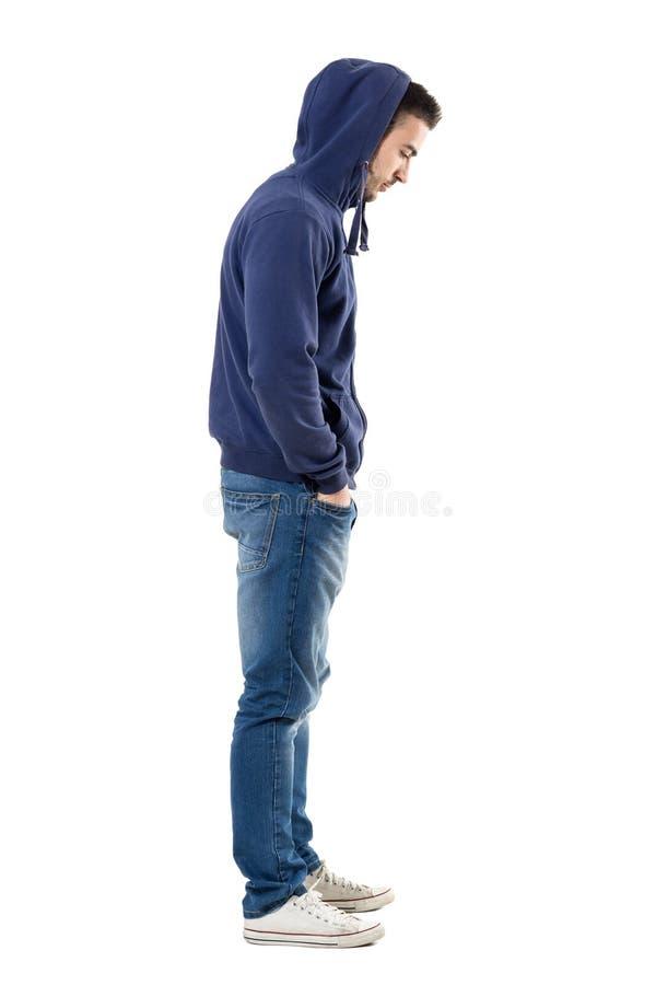 Opinião lateral o homem triste da virada na camisa encapuçado com mãos em uns bolsos que olham para baixo foto de stock