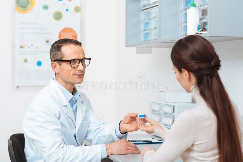 opinião lateral o oftalmologista nos monóculos que dão a lente de contato ao paciente foto de stock royalty free