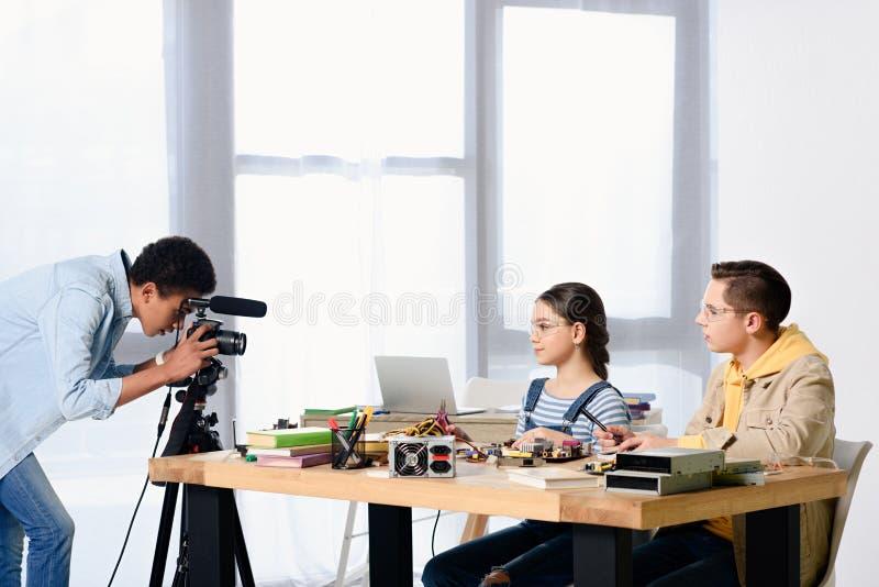 opinião lateral os adolescentes multiculturais que disparam no blogue video sobre a engenharia imagem de stock royalty free