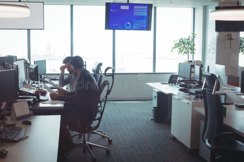 Opinião lateral os colegas masculinos do negócio que trabalham junto no escritório fotografia de stock