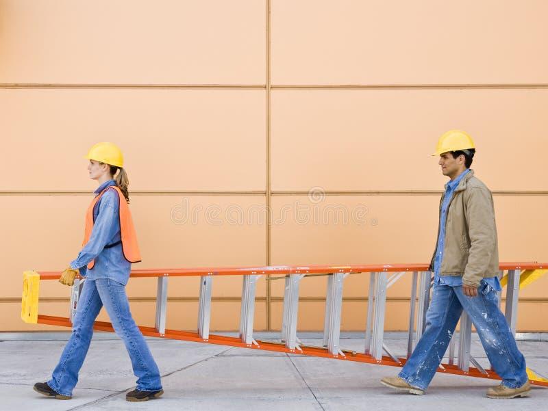 Opinião lateral os trabalhadores da construção que carreg a escada imagens de stock royalty free