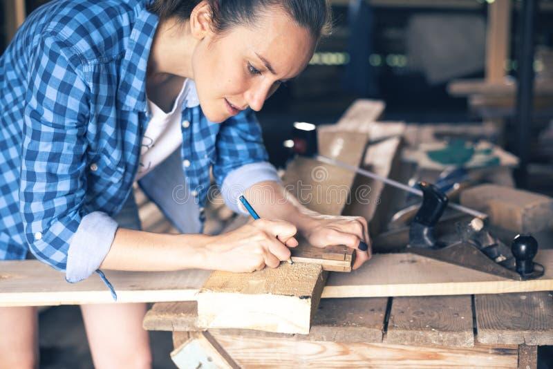 A opinião lateral um carpinteiro da mulher tira em uma linha de corte da placa de madeira imagem de stock
