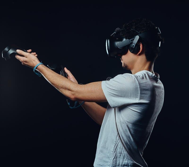 Opinião lateral um homem com a cerda vestida na camisa branca que joga jogos com os óculos de proteção da realidade virtual fotografia de stock