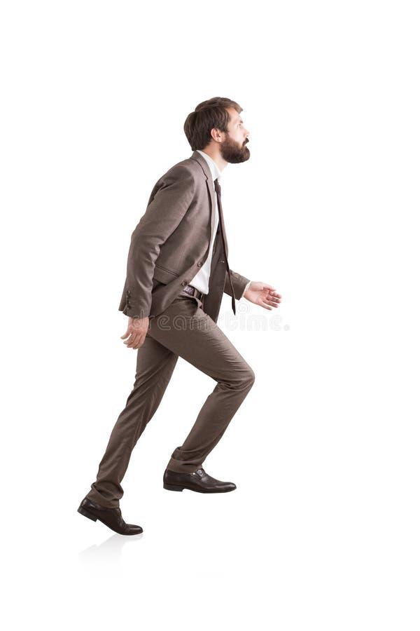 Opinião lateral um homem de negócios que escala uma escada invisível imagem de stock