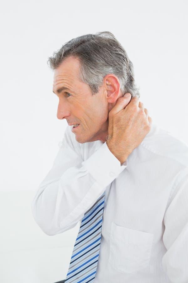 Opinião lateral um homem maduro que sofre da dor de pescoço fotos de stock