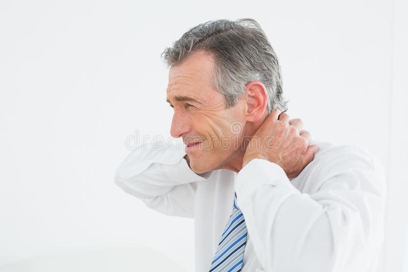 Opinião lateral um homem maduro que sofre da dor de pescoço fotografia de stock