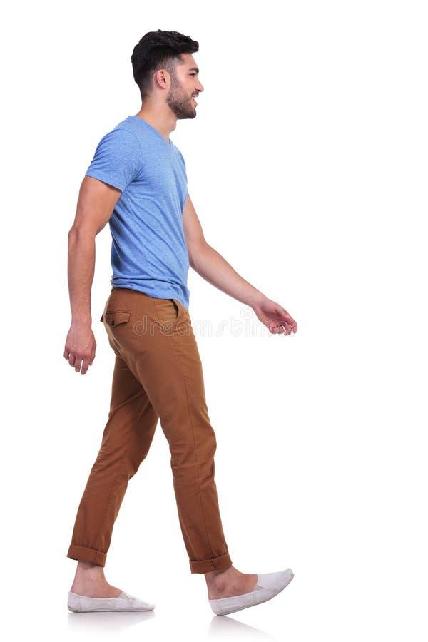 Opinião lateral um homem ocasional que anda para a frente e que sorri fotos de stock royalty free