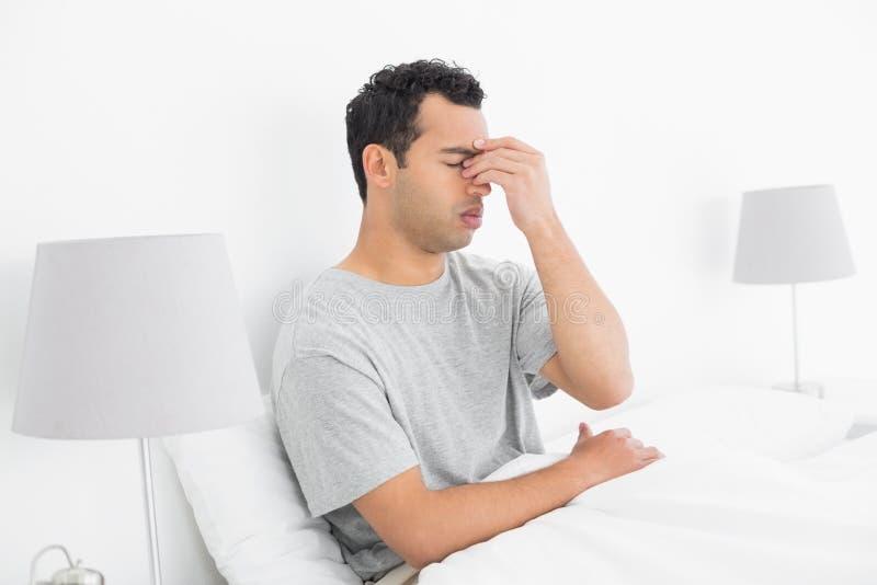 Opinião lateral um homem pensativo que senta-se na cama fotografia de stock