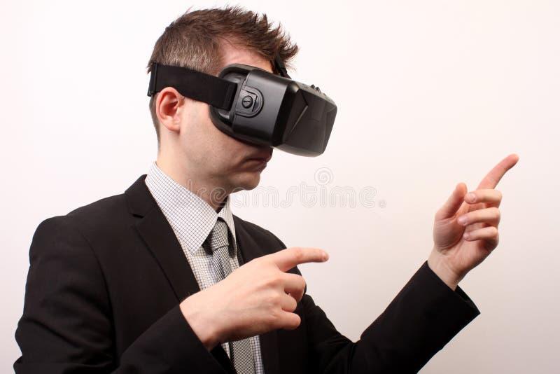 Opinião lateral um homem que veste uns auriculares da falha 3D de Oculus da realidade virtual de VR, tocando ou apontando em algo imagem de stock