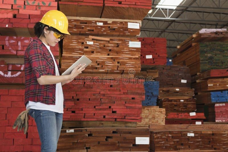 Opinião lateral um trabalhador industrial fêmea asiático que trabalha no PC da tabuleta com as pranchas de madeira empilhadas no f foto de stock royalty free
