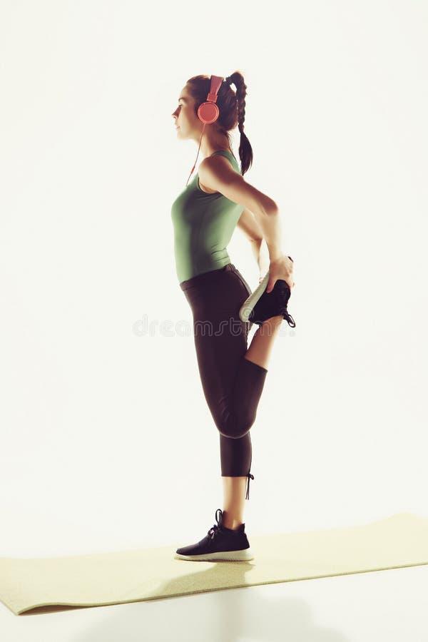A opinião lateral uma jovem mulher que estica o corpo na classe da ginástica foto de stock