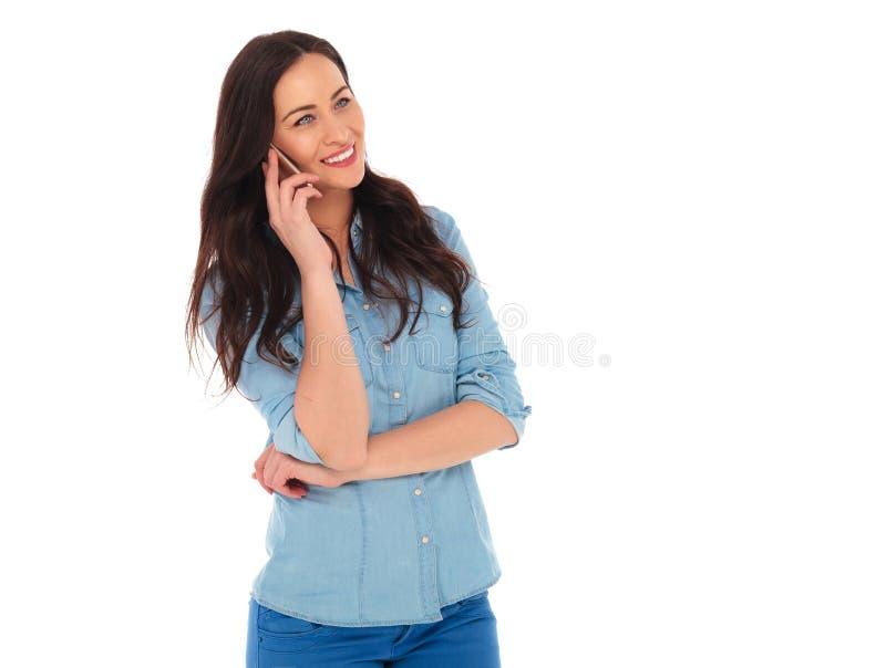 Opinião lateral uma jovem mulher que fala no telefone foto de stock royalty free