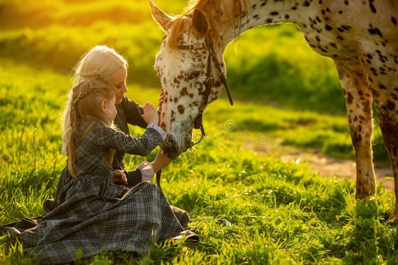 Opinião lateral uma mãe nova com uma menina no curso dos vestidos um cavalo manchado em um prado verde imagens de stock royalty free