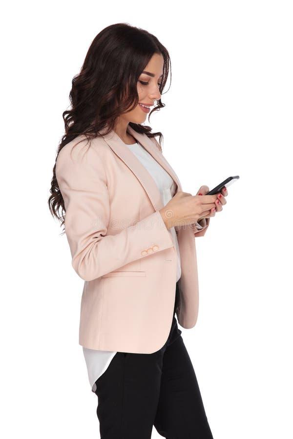 Opinião lateral uma mulher de negócio nova que texting nela fotografia de stock