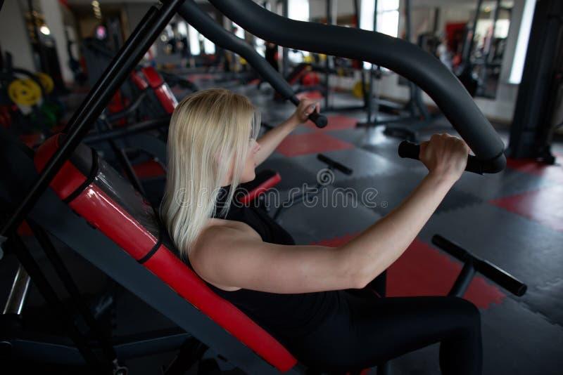 Opinião lateral uma mulher desportiva nova no sportswear no gym A menina executa exercícios do tríceps em um estúdio da aptidão fotos de stock royalty free