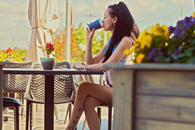 A opinião lateral uma mulher magro bonita com uma tatuagem em seu pé bebe o café ao sentar-se no terraço no café do ar livre fotos de stock